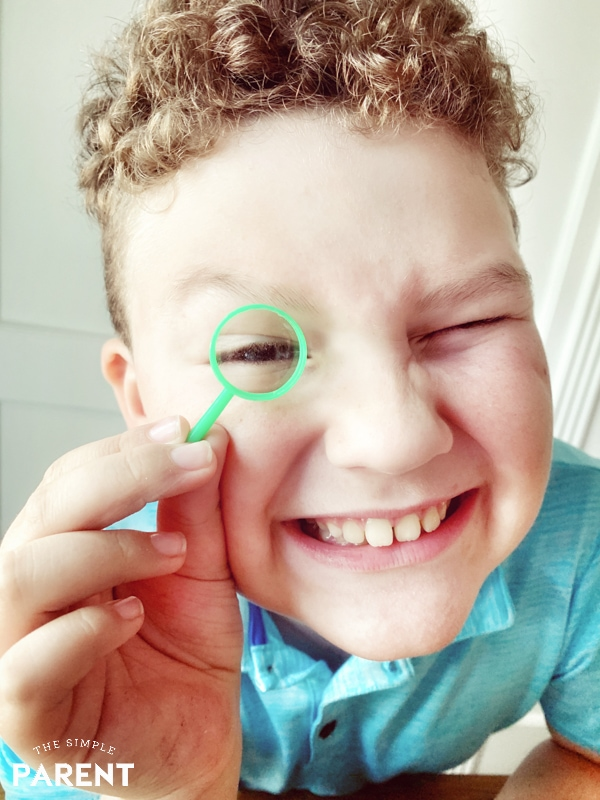 Boy playing with magnifying glass from Scientific Explorer® Disgusting Biology Kit