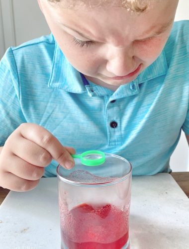 Boy looking at glass of fake blood made with the Scientific Explorer® Disgusting Biology Kit