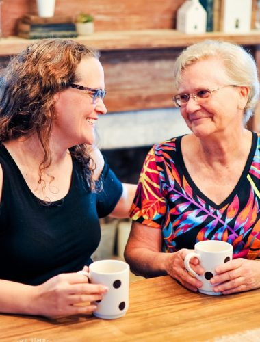 Mother and daughter having coffee at table