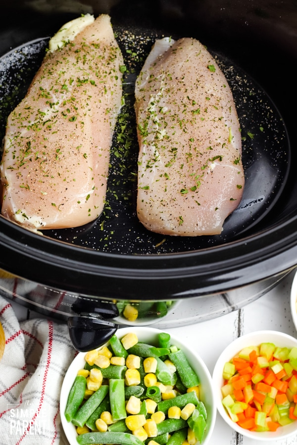 Chicken breasts in a slow cooker with frozen vegetables in bowls