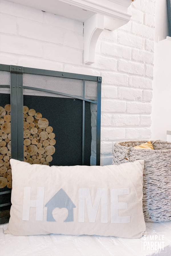 "Pillow that says ""Home"" sitting on a white fireplace"