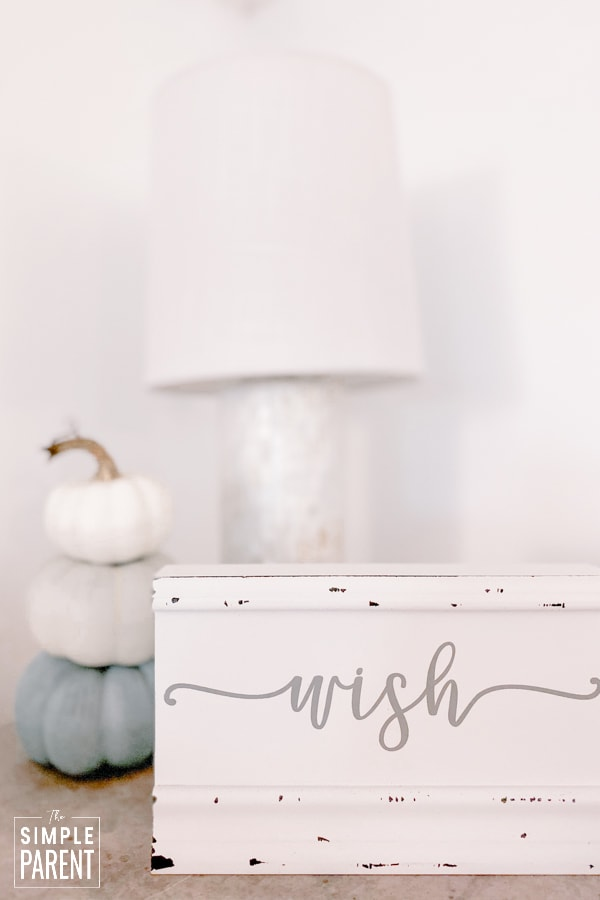 "Wood sign that says ""Wish"" sitting on table in front of a lamp"