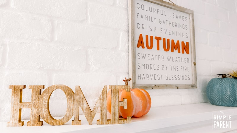Wooden home sign sitting on mantle of white fireplace