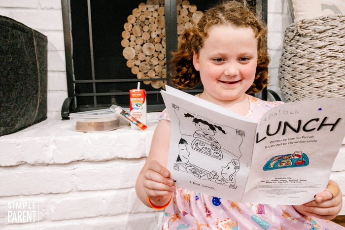 Girl reading book about school lunch
