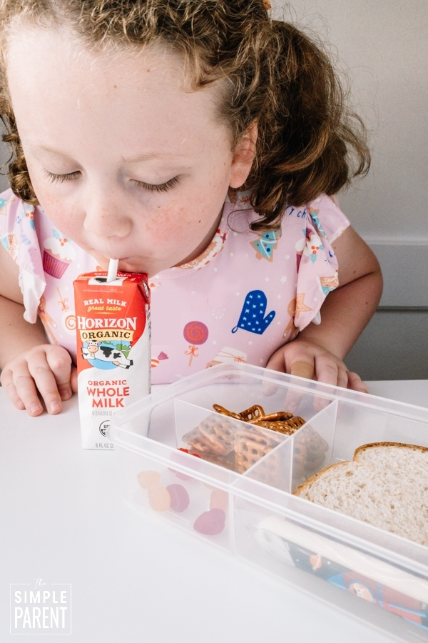 Girl drinking Horizon Organic milk with a packed school lunch.