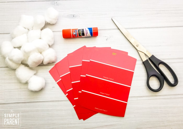 Cotton balls, red paint chip samples, glue stick and scissors