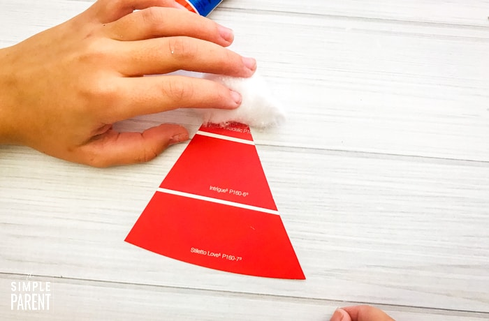 Gluing cotton ball on red triangle