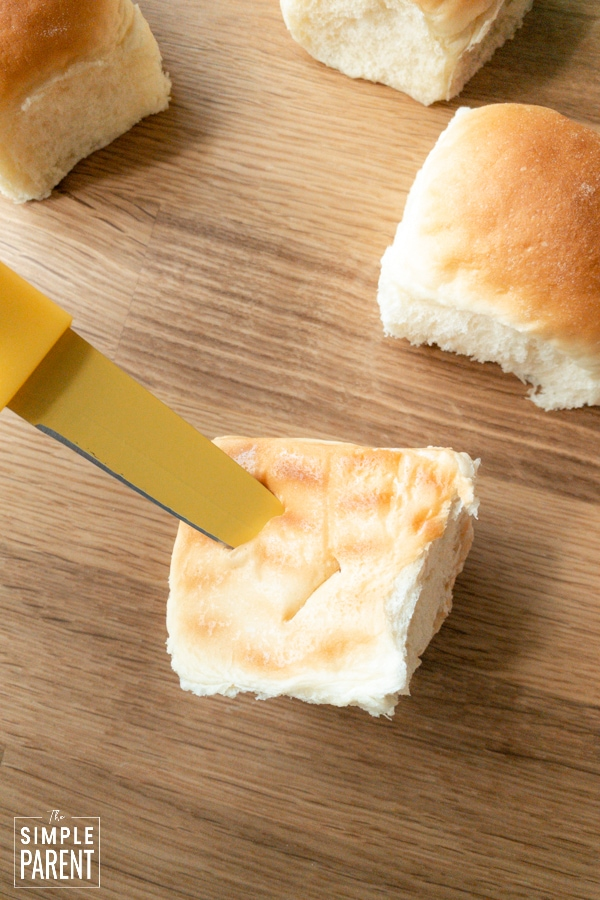 Knife cutting bottom of a dinner roll