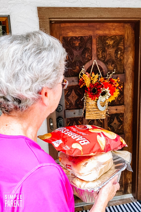 Older woman waiting at front door of house with a meal
