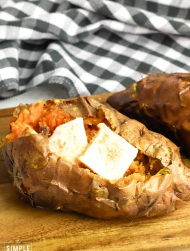 Air Fryer Sweet Potato with butter sitting on a cutting board with a black and white napkin