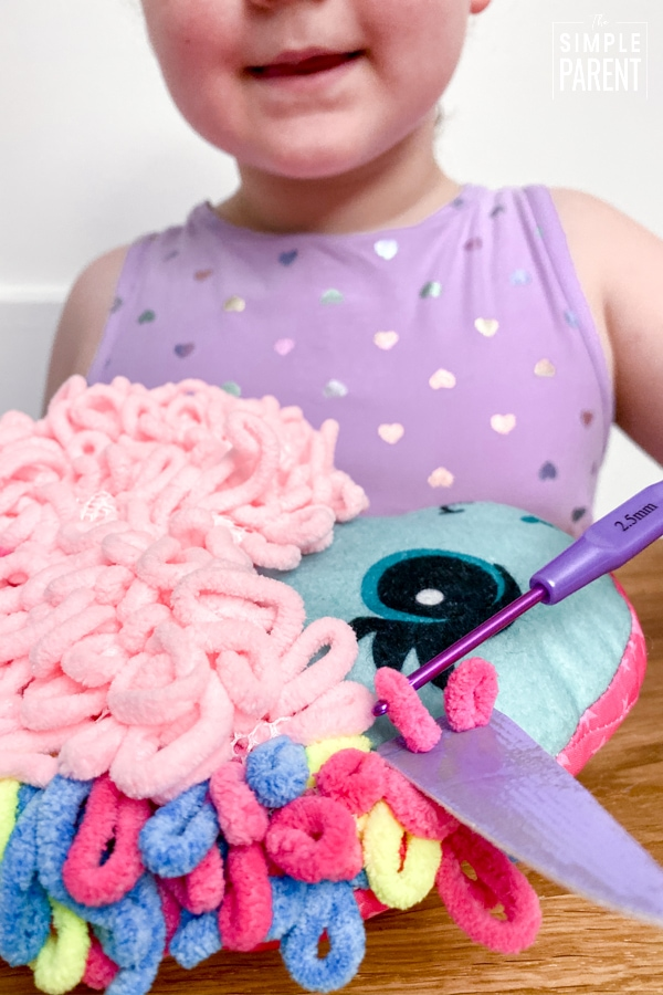 Girl making a Loopies plush unicorn