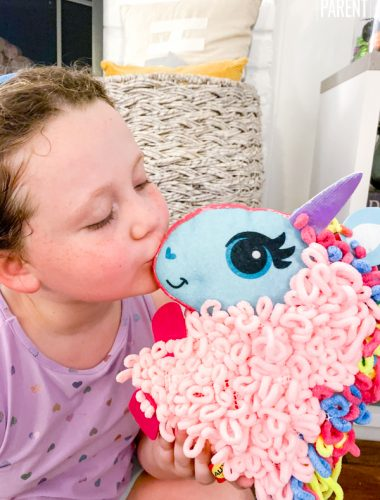 Girl kissing a plush unicorn