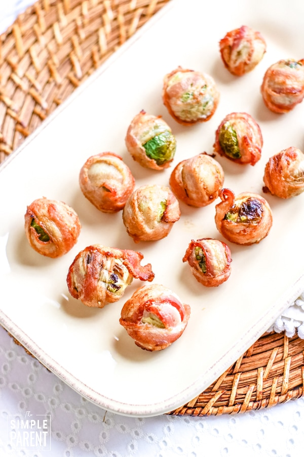 Bacon wrapped Brussel sprout appetizer on white serving dish