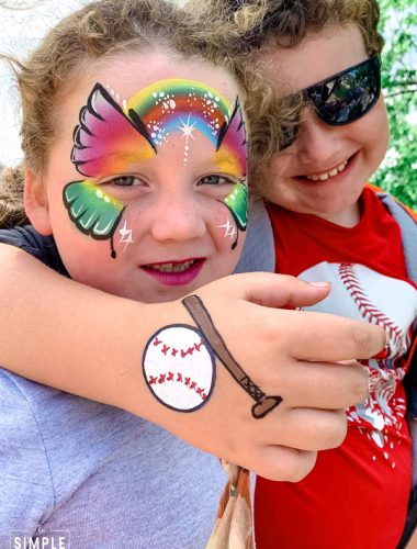 Brother and sister with face painting of a butterfly and a baseball