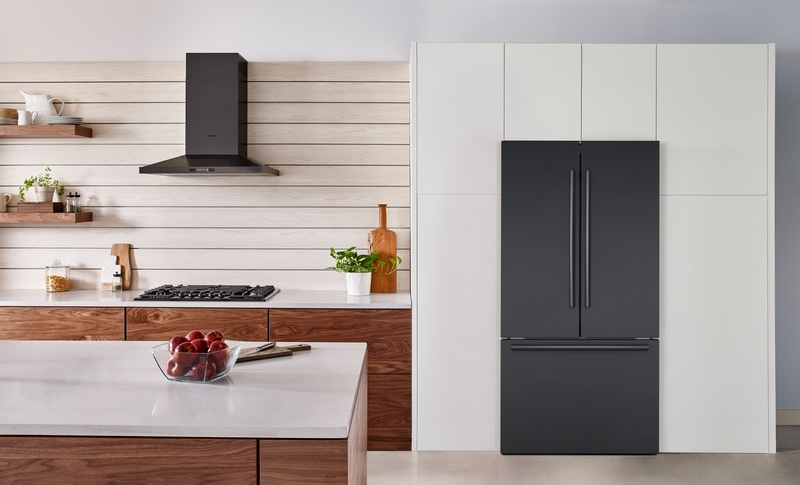 Black Bosch counter depth fridge in a white and brown kitchen