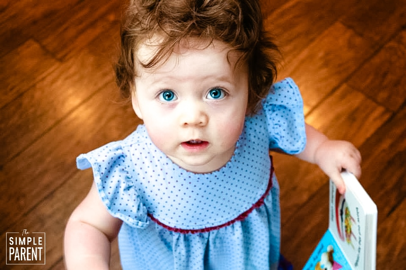 Toddler girl wearing blue dress with purple polka dots and holding a book
