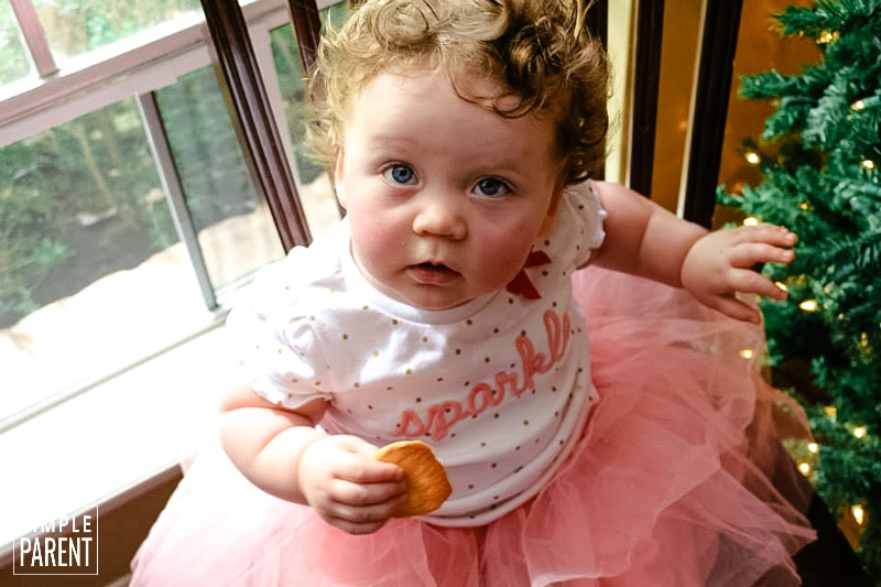 Little girl wearing a pink tutu and eating a cookie