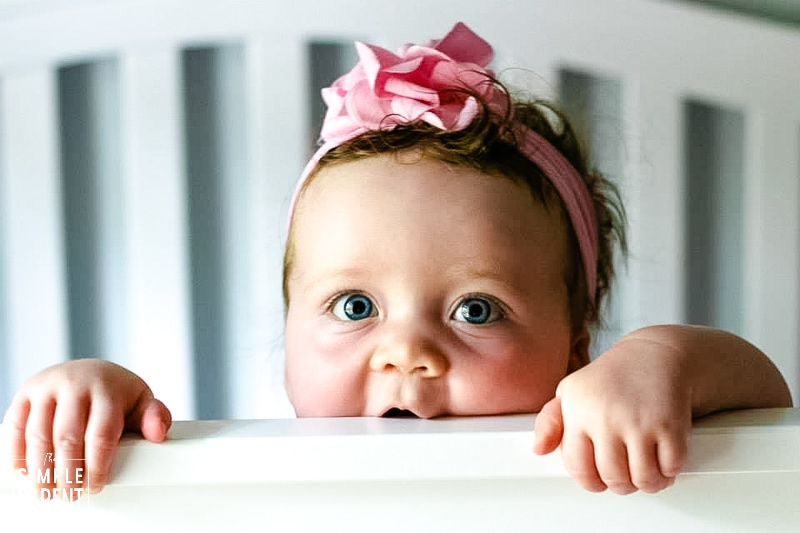 Baby girl with pink bow on, biting the edge of a white crib