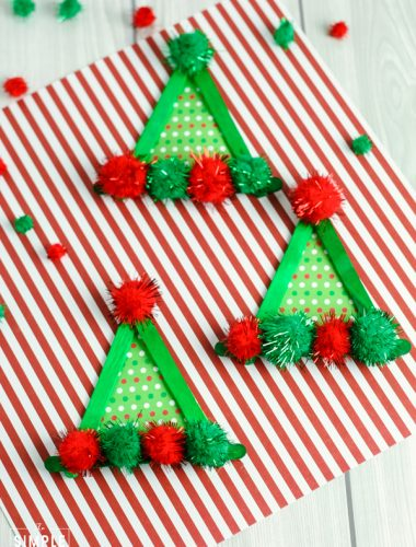 Elf hat craft made out of green craft sticks, striped scrapbook paper and pom-poms