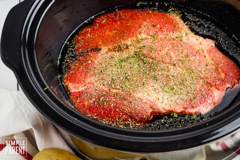 Chuck roast in a Crockpot and sprinkled with seasoning before being cooked