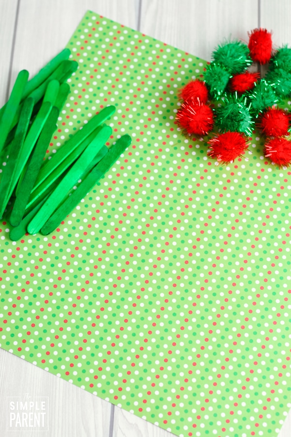 Materials to make Elf hats including scrapbook paper, craft sticks, and pom-poms