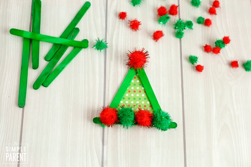 Triangle made out of green craft sticks with red and green pom poms glued on to look like an elf hat