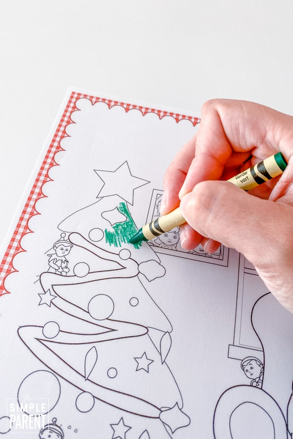 Hand coloring a Christmas coloring page with a green crayon