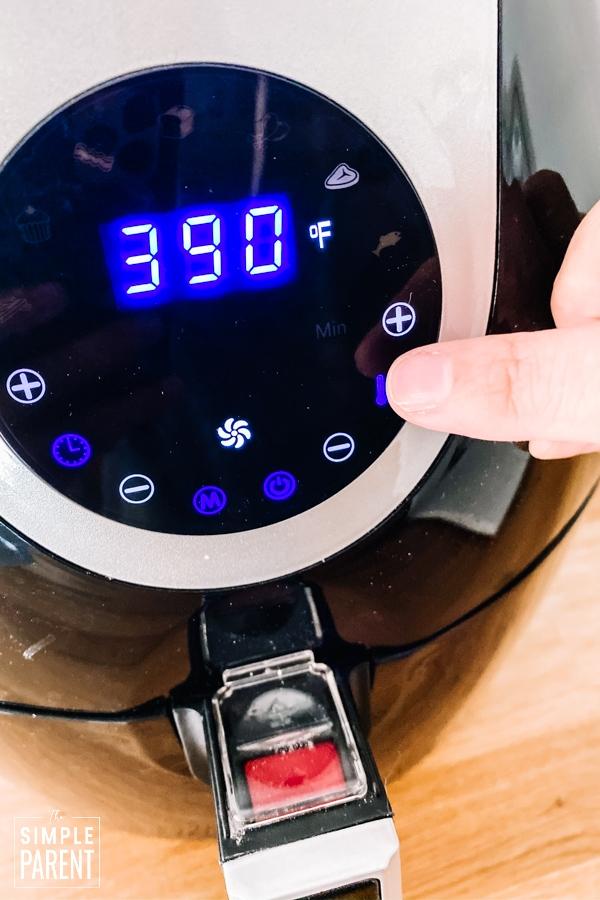 Finger pressing temperature button on an air fryer