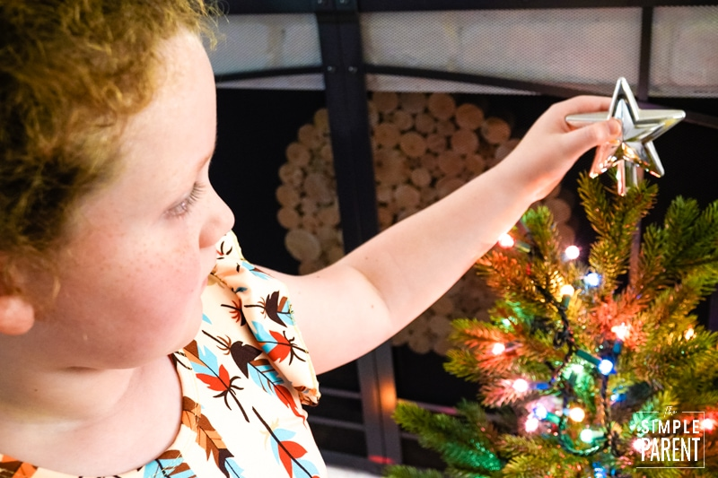 Young girl putting a silver star on top of a little Christmas tree
