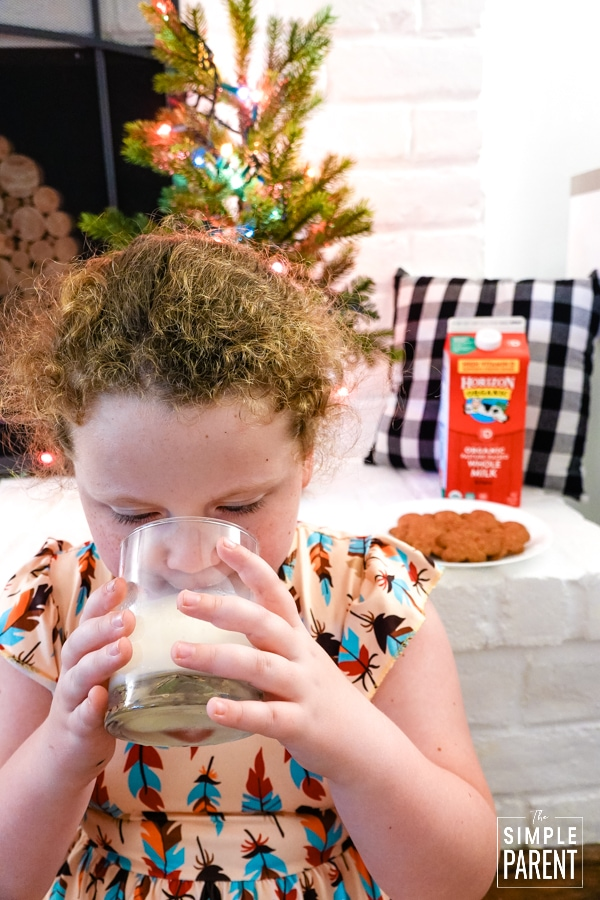 Girl drinking a glass of milk in front of a white fireplace