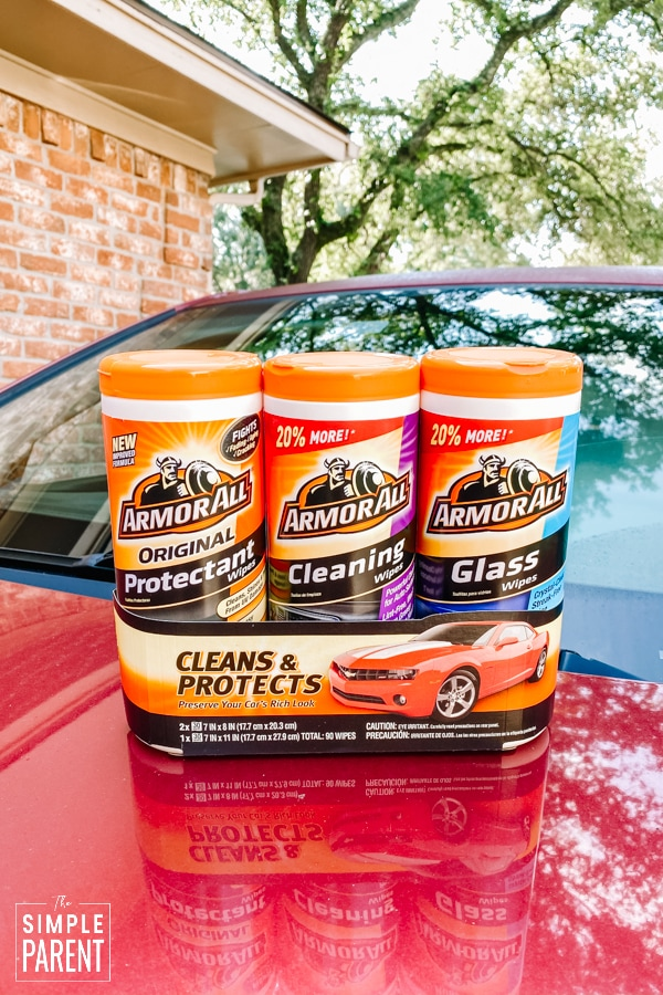 Armor All cleaning wipes 3 pack sitting on hood of a red car