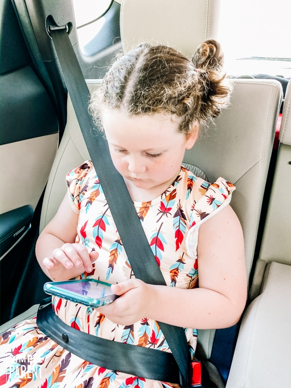 Girl sitting in the back seat of a car playing on a phone