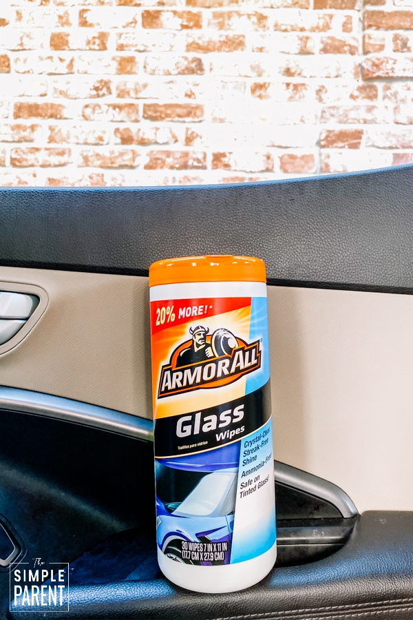 Canister of Armor All Glass wipes sitting on the arm rest in a car