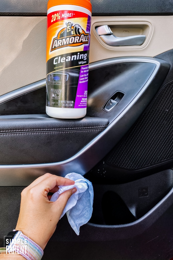 Cleaning the inside of the car door with a wipe