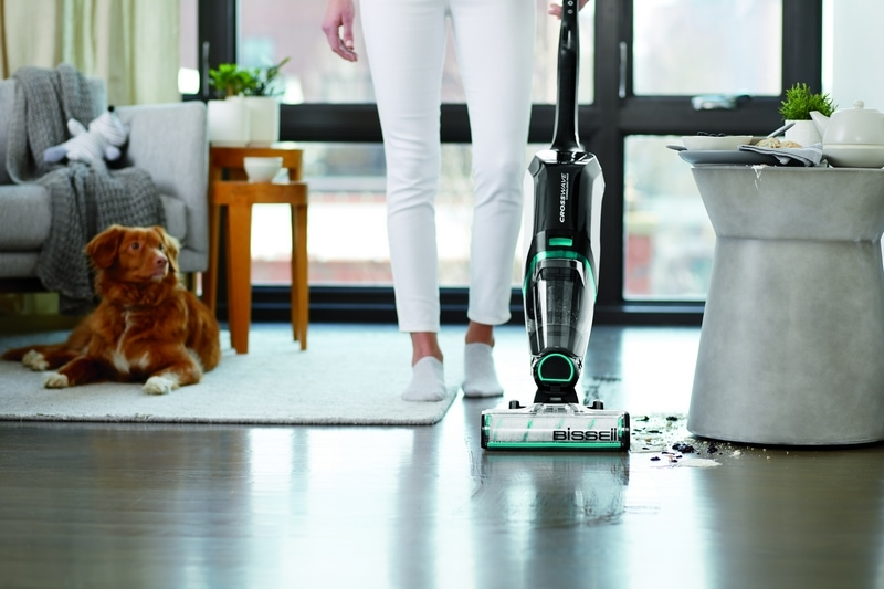 Woman vacuuming floor while dog lays on the rug next to her