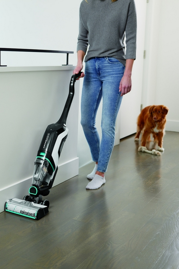 Woman vacuuming floor while dog follows behind her
