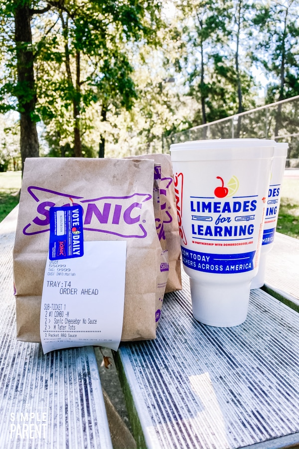 Bag of food and drinks from SONIC Drive-In sitting on a picnic table