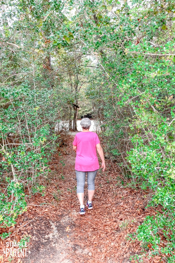 Senior aged woman in exercise clothes walking away down a path through trees