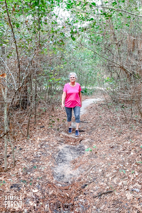 Older woman walking on path through trees