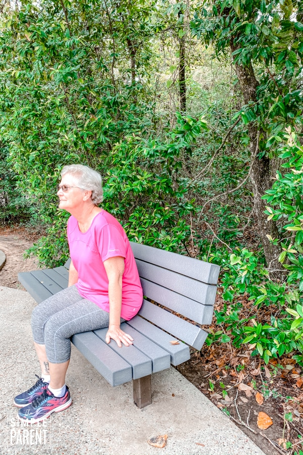 Grandmother wearing exercise clothes and sitting on a park bench