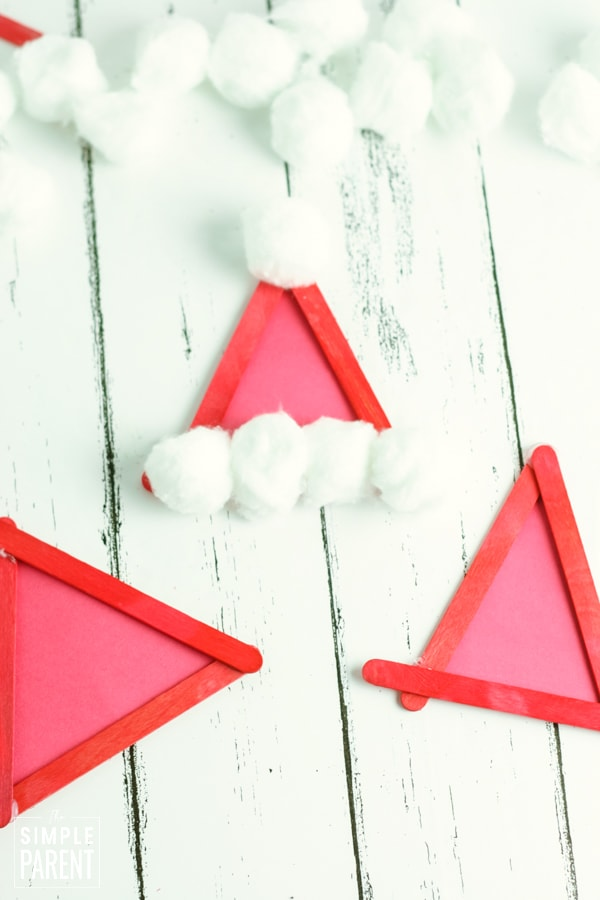 Red craft stick triangles with cotton balls on the side to make a Santa hat
