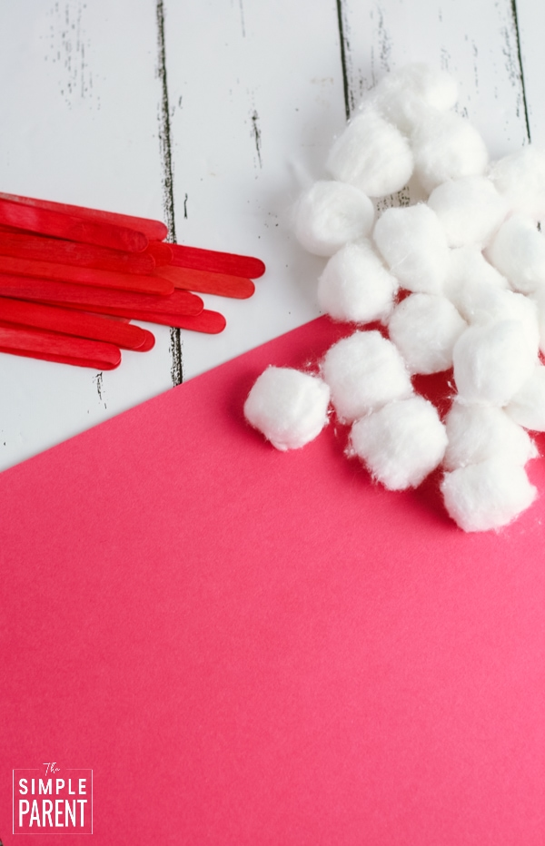 Materials to make Santa hat craft with red paper, red popsicle sticks and cotton balls