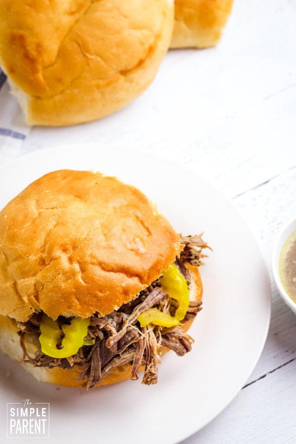 Slow Cooker Italian Beef sandwich with banana peppers on a white plate