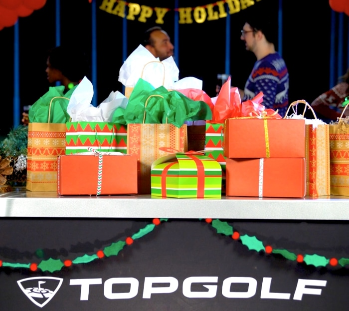 Stack of Christmas presents on a table with a Topgolf sign