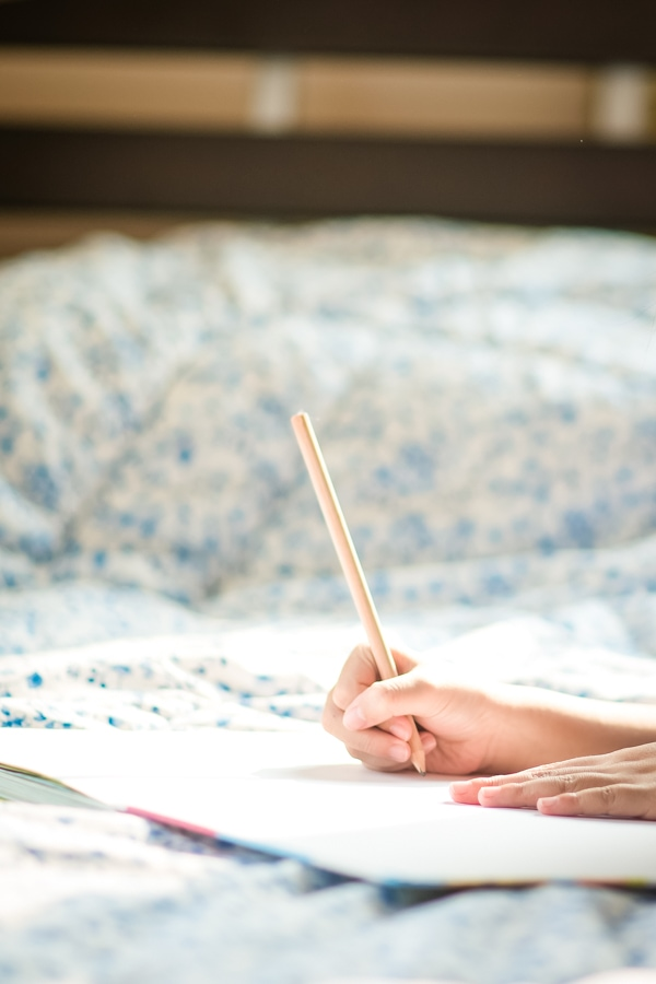 Girl using a pencil to write in a journal while laying on a bed