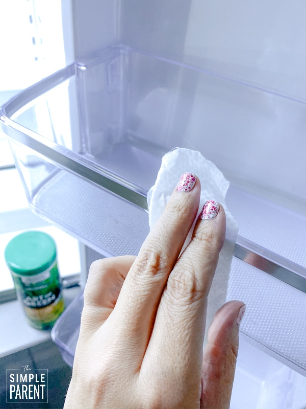 Hand using a cleaning wipe to wipe off a shelf in a refrigerator