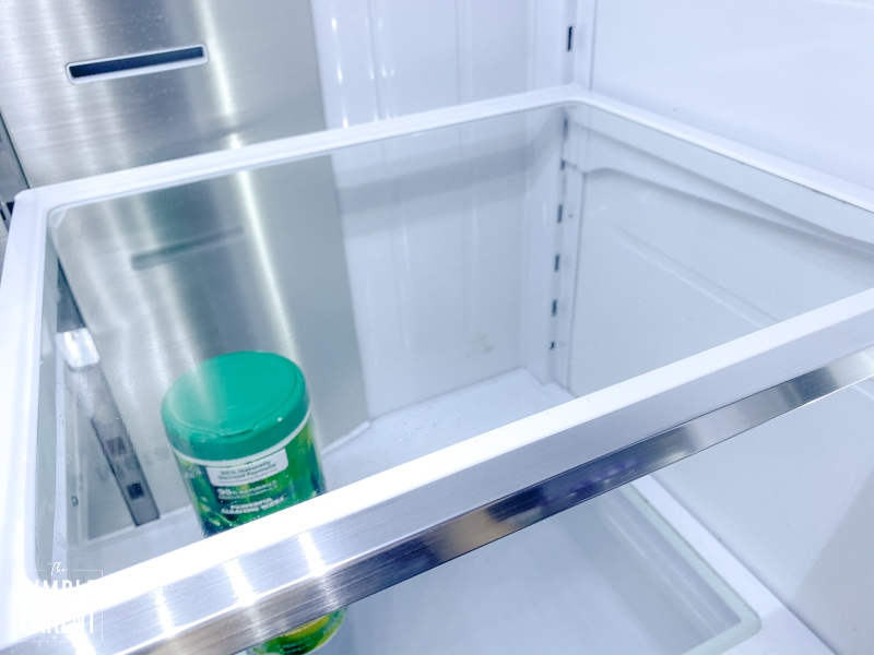 Clean refrigerator shelf with a container of cleaning wipes sitting on the shelf below