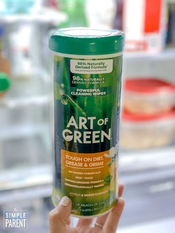 Container of Art of Green cleaning wipes in front of an open refrigerator