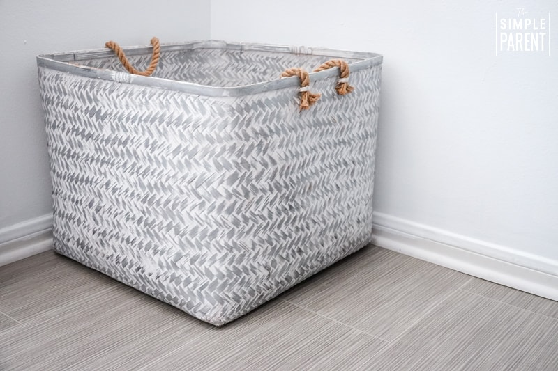 Large gray and white basket sitting in the corner of a bedroom