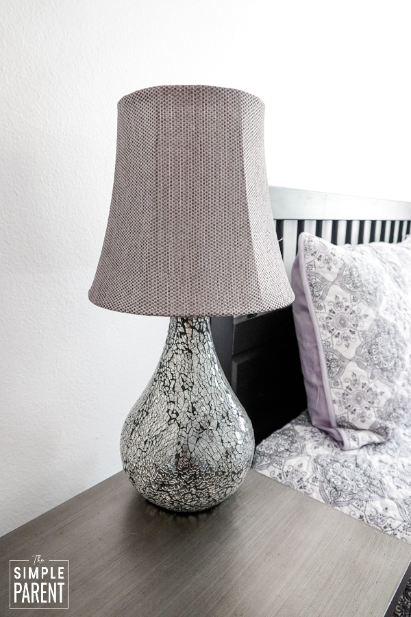 Gray lamp with a base of crackled glass sitting on a gray nightstand